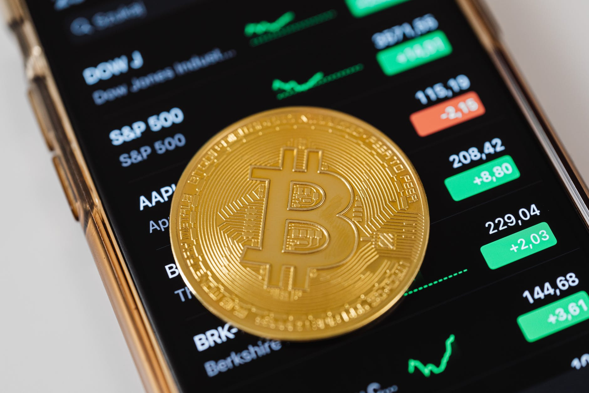 how to make profit on cryptocurrencies: phone screen with stocks and Bitcoin